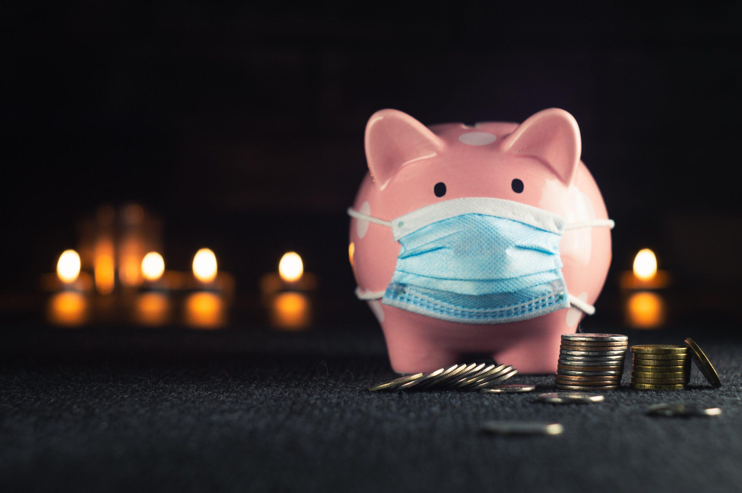 skarbonka świnka w maseczce z wysypanymi monetami