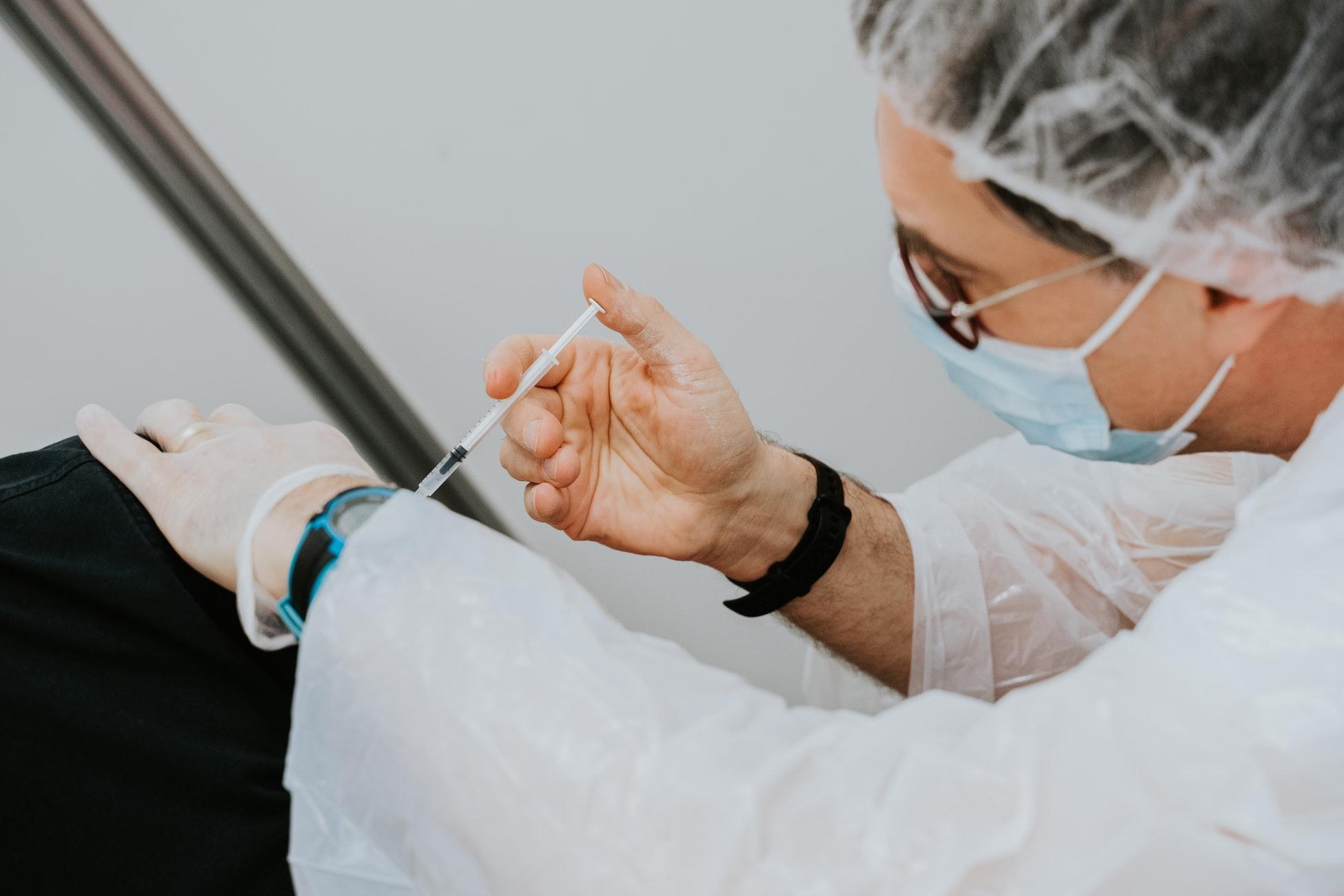 lekarz robiący zastrzyk pacjentowi