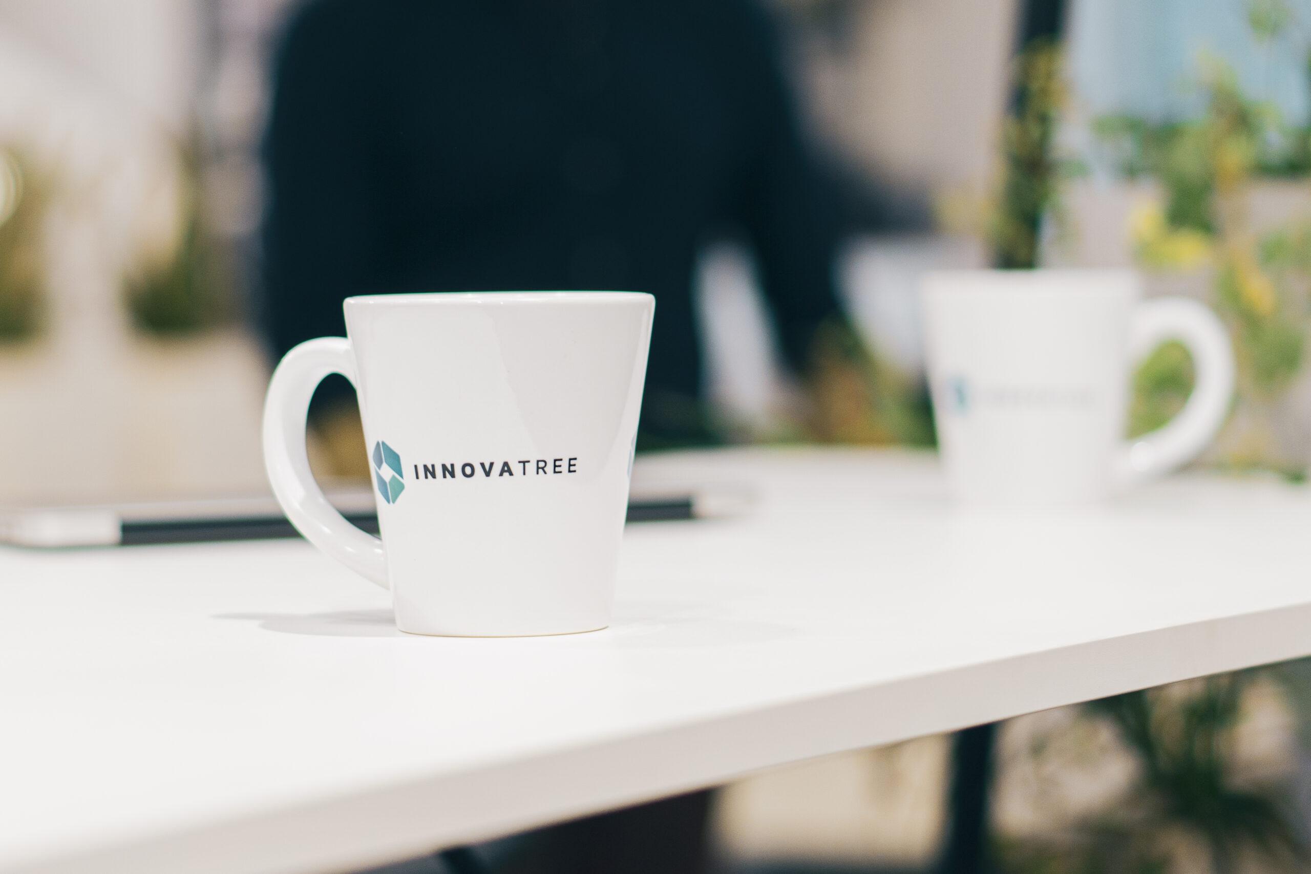 biały kubek z logo innovatree