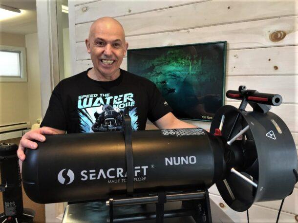mężczyzna trzymający skuter podwodny seacraft