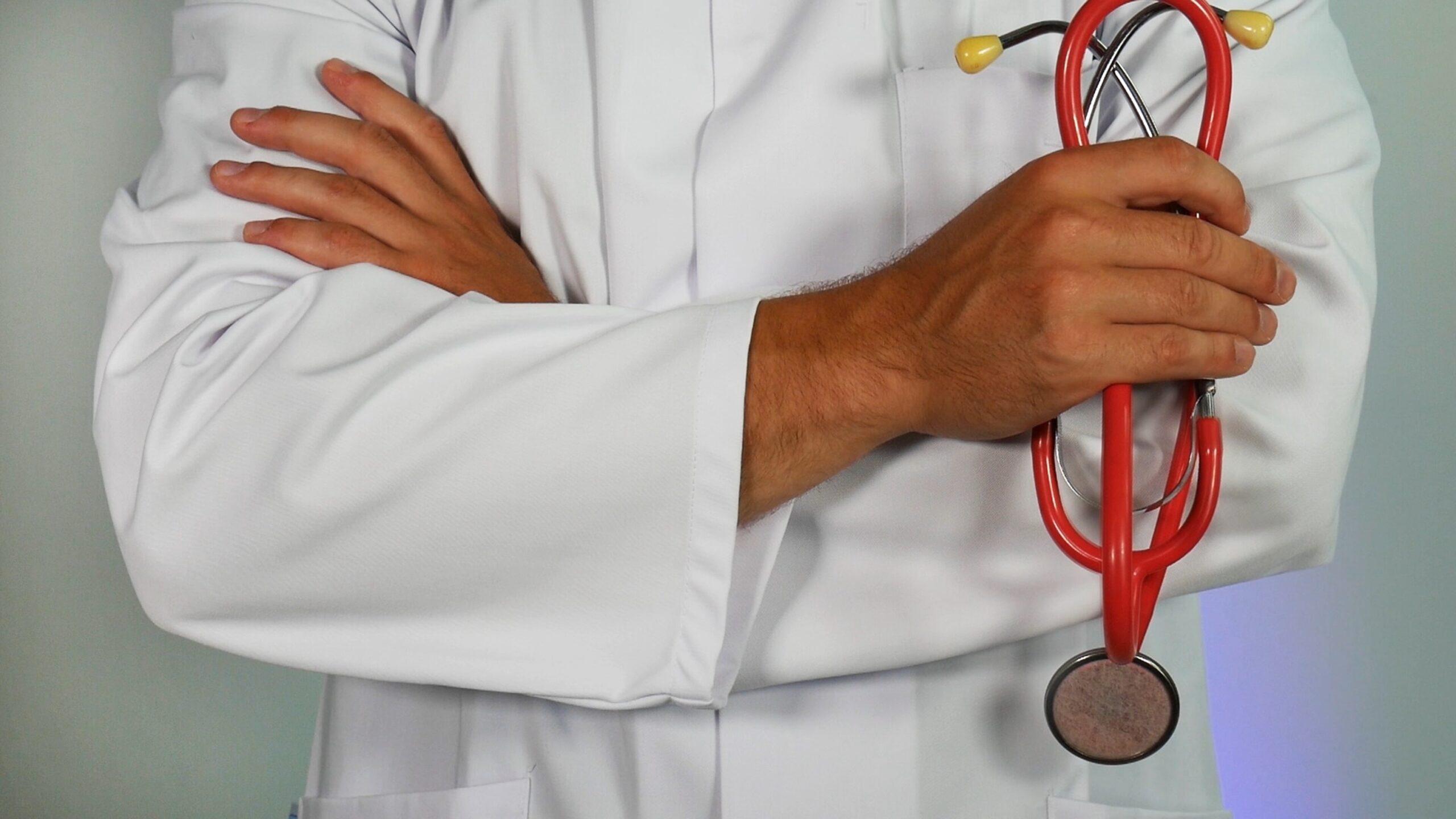 lekarz w kitlu trzymający czerwony stetoskop