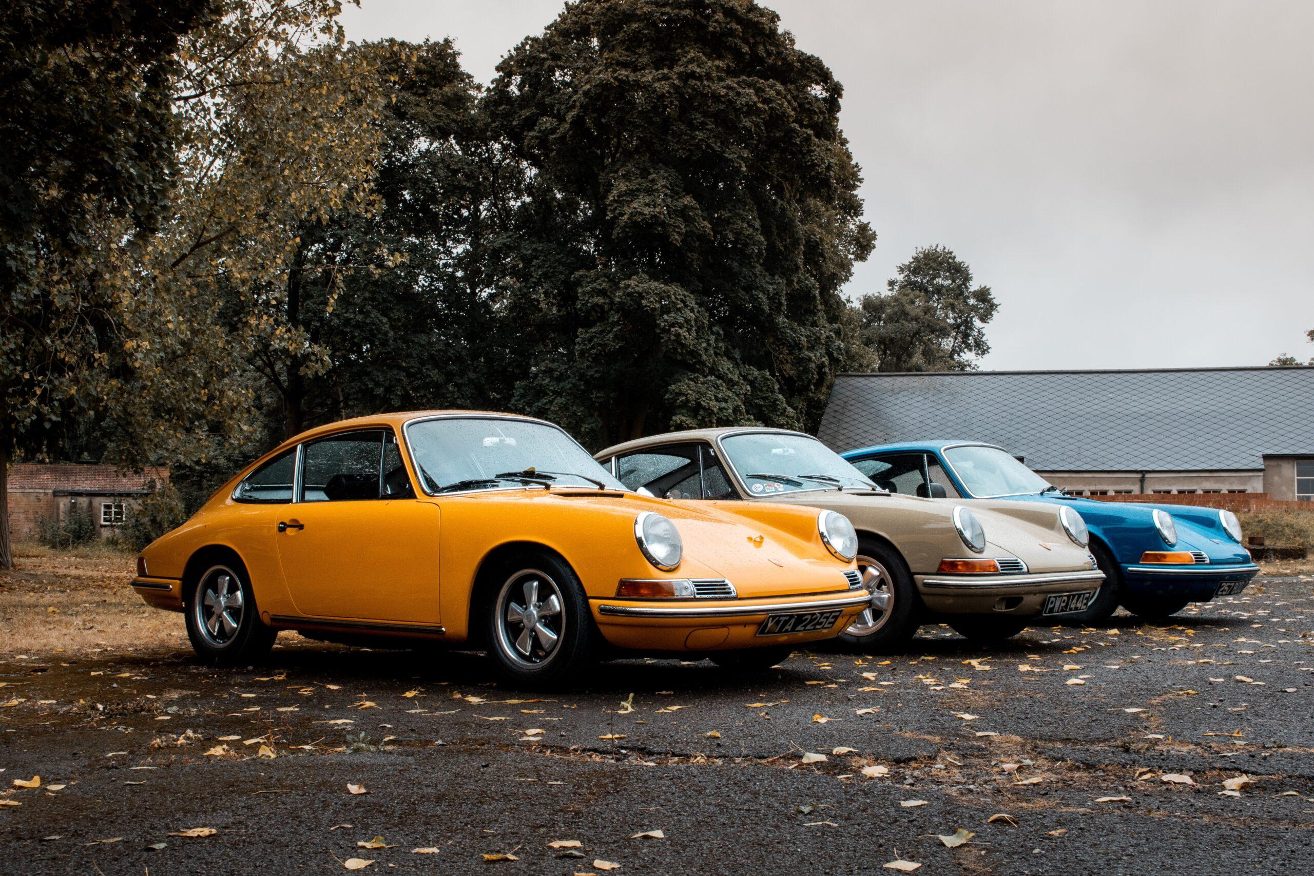 trzy zaparkowane zabytkowe auta