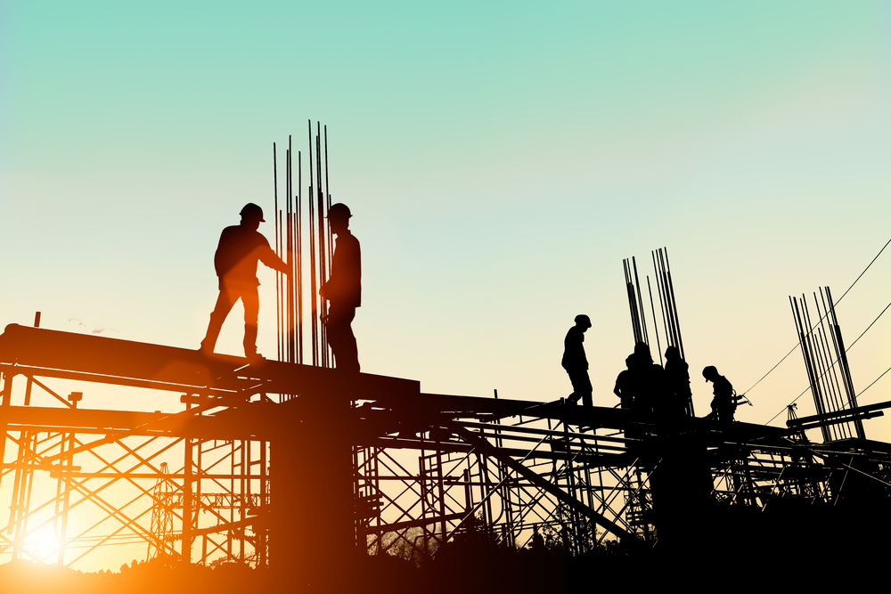 robotnicy na rusztowaniu o wschodzie słońca