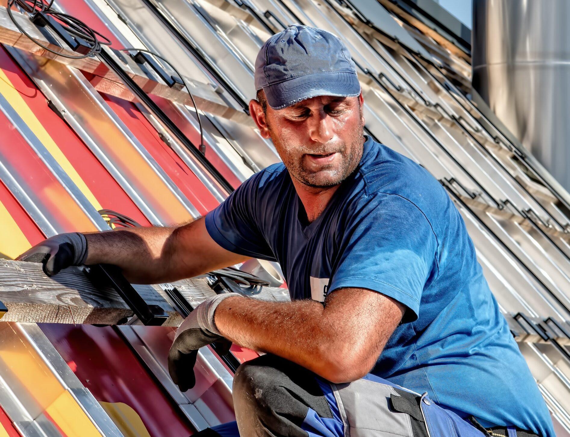 pracownik budowlany montujący dach